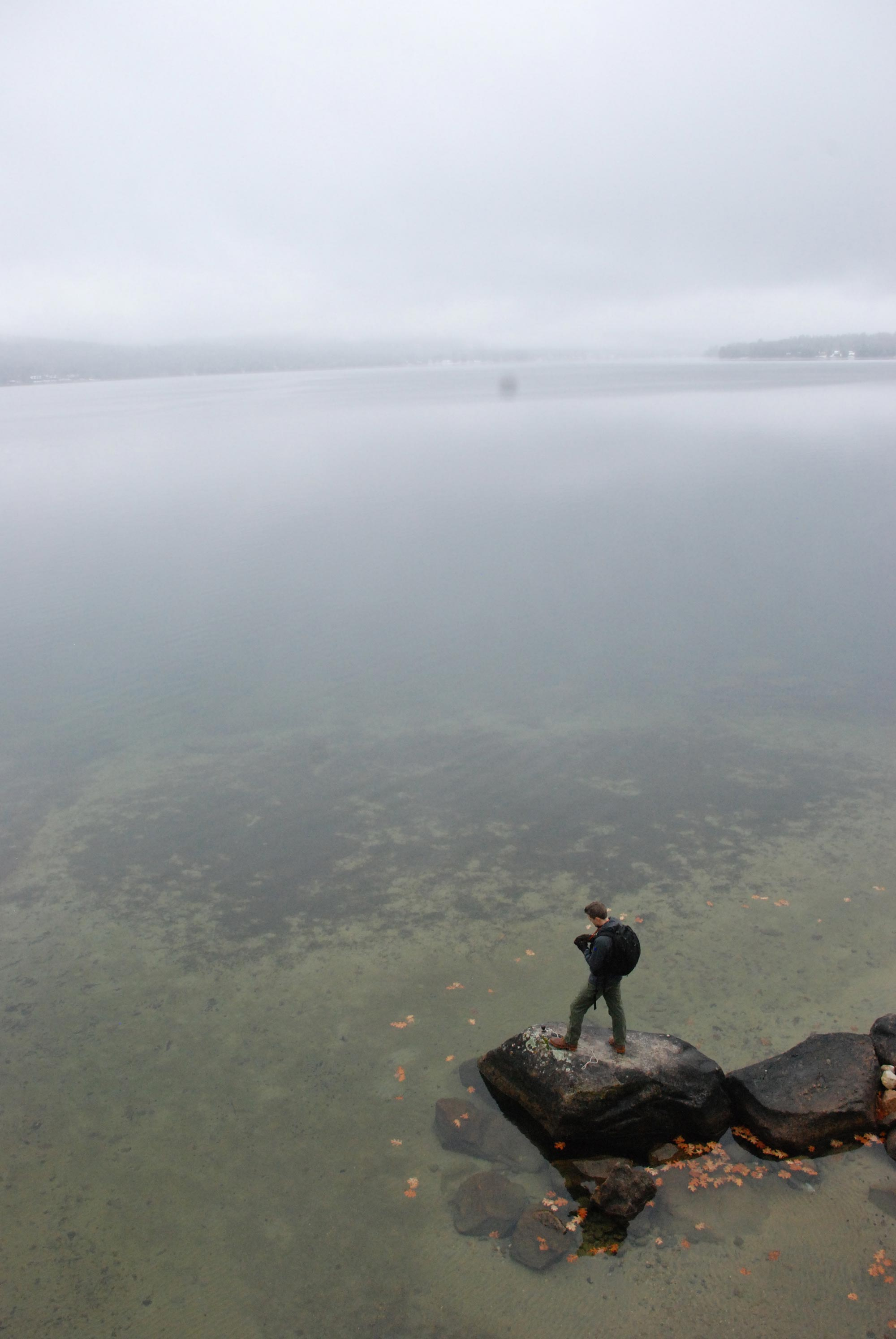 A man stands at the edge of a misty lake, with compass in hand.
